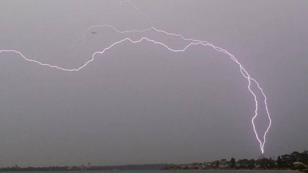 Lightning seems to threaten a plane and the BHP tower over Perth.