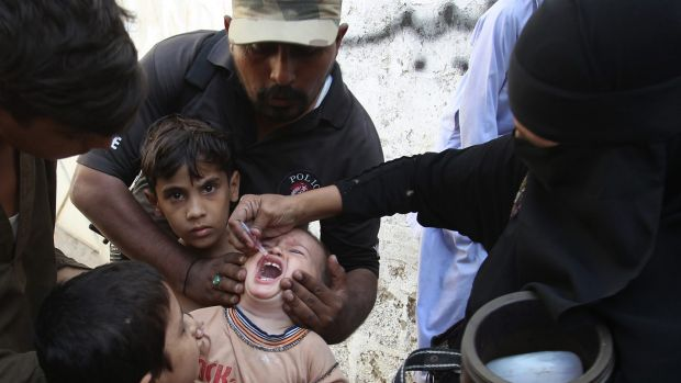 Brave work: A Pakistani police officer helps a health worker to give polio vaccine to a child in Karachi, Pakistan.