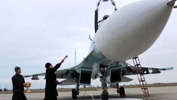 A Russian orthodox priest blesses a SU-27 SM fighter jet on the airfield of Belbek military airport outside Sevastopol, ...
