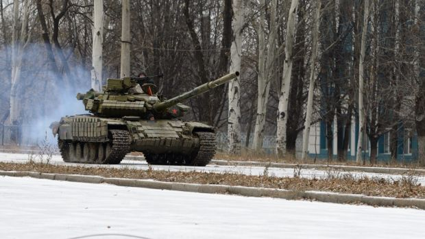 A Russian T-72 tank without a licence plate and coming from Donetsk airport area moves along a snow-covered avenue in ...