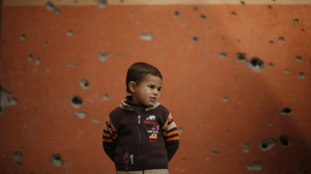 A Palestinian boy stands outside a mosque witnesses said was damaged by Israeli shelling.