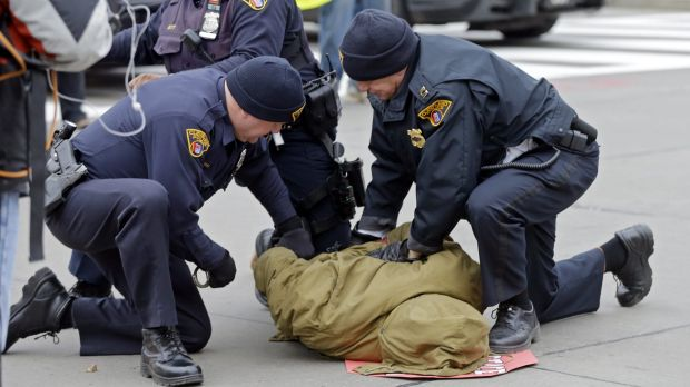 Police arrest a demonstrator protesting against the police shooting of a 12-year-old boy who was fatally shot by a ...