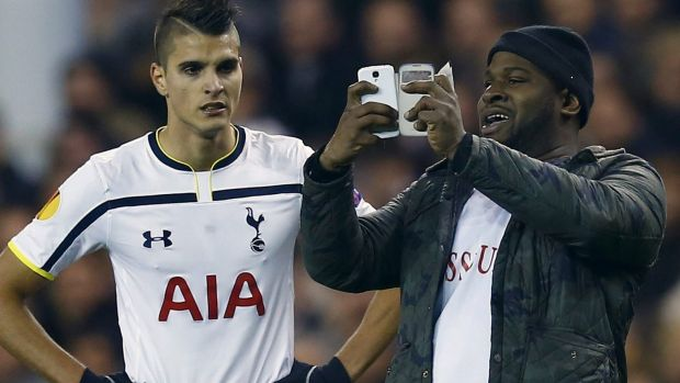 A spectator runs onto the pitch and takes a 'selfie' of himself and Tottenham Hotspur's Erik Lamela.