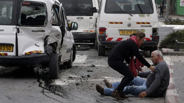 A wounded man sits on the street after a vehicle attack by a Palestinian motorist in Jerusalem in which a policeman was ...