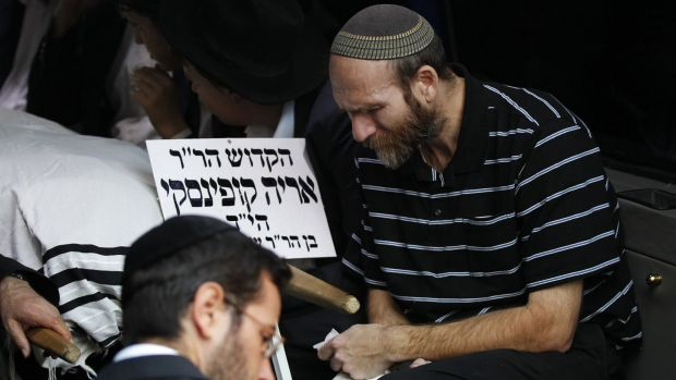 A mourner sits beside the body of Aryeh Kopinsky, one of the five victims of the Har Nof synagogue attack, during his ...