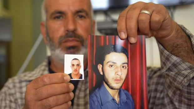A relative with photos of the Har Nof synagogue attackers, Ghassan (right) and Uday Abu Jamal, outside the family home ...