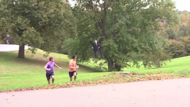 Grim message: Joggers run away from a drone involved in a Halloween prank posted on YouTube.