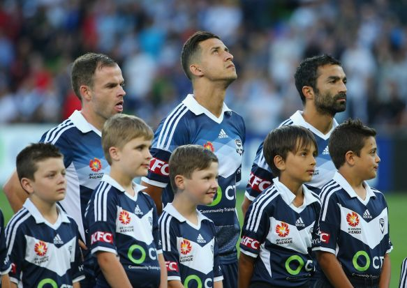 Victory players observe the minute's silence during the round eight A-League match between Melbourne Victory and ...