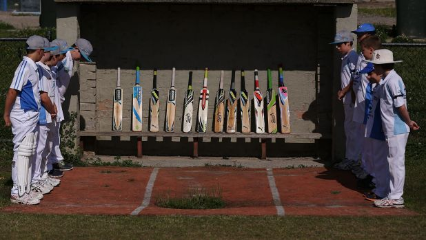 Langwarrin under-12  cricketers pay their respects to the memory of Phillip Hughes by standing their bats.