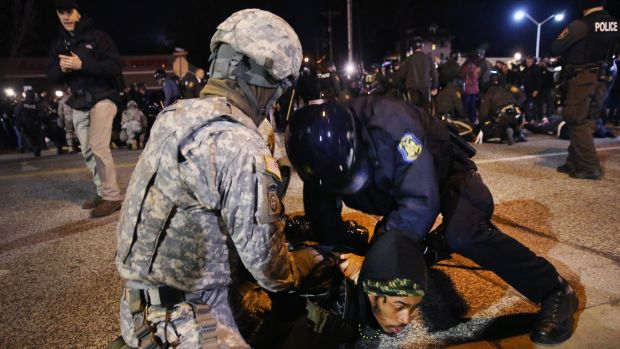 Police and national guard arrest a demonstrator outside the police station November 28, 2014 in Ferguson, Missouri.