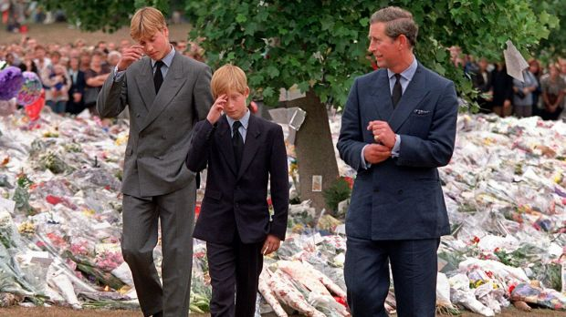 Princes William and Harry with their father Prince Charles walk among floral tributes in the wake of Diana's death.