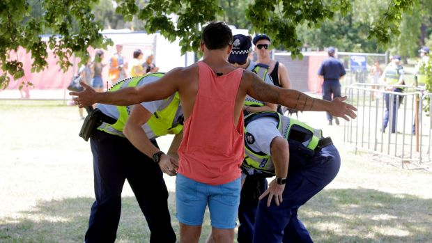 A festival goer is searched for drugs by police.
