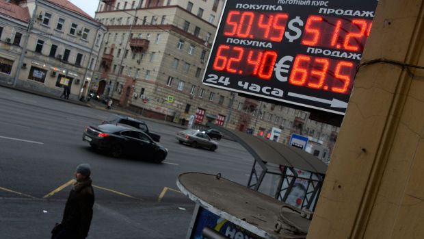 Shrugging it off: Russians are smiling despite a plunge in the rouble exchange rate.