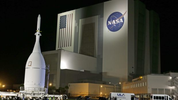 Great expectations: The Orion spacecraft moves by the Vehicle Assembly Building on its journey to Space Launch Complex ...