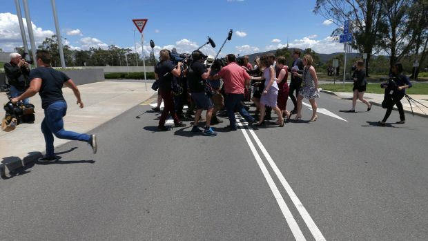 Senator Ricky Muir attempts to escape media attention outside Federal Parliament on Tuesday.