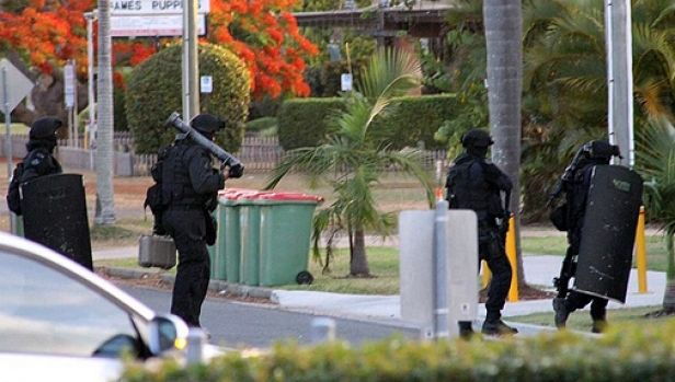 Officers in full riot gear prepare to enter the Passage Street unit block where a man in his forties has barricaded ...