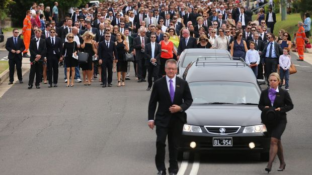Procession: Mourners walk behind the hearse at Phillip Hughes' funeral in Macksville.