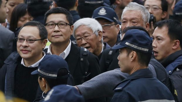Four protest leaders, from left, Benny Tai Yiu-ting, Chan Kin-man, Joseph Zen and Chu Yiu-ming, surrounded by police ...
