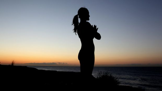 Popular as fitness around the world: A woman enjoys some early-morning yoga at Coogee Beach.