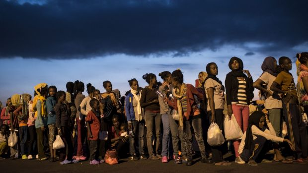 Fleeing multitudes: Hundreds of migrants from sub-Saharan Africa arrive at Augusta port in Sicily in September.