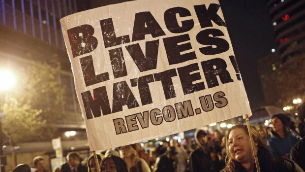 Protesters hold a sign during a march against the New York City grand jury decision to not indict the police officer in ...