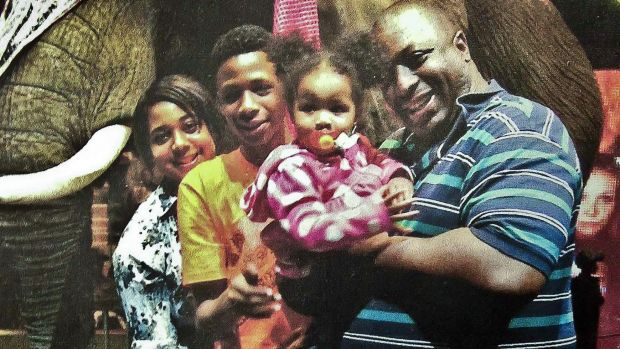 Death by police chokehold: Eric Garner, right, poses with his children during a family outing.