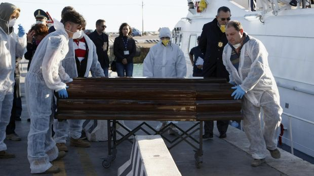 Tragedy: A coffin containing the body of a migrant who died in an inflatable boat on the Strait of Sicily is carried off ...