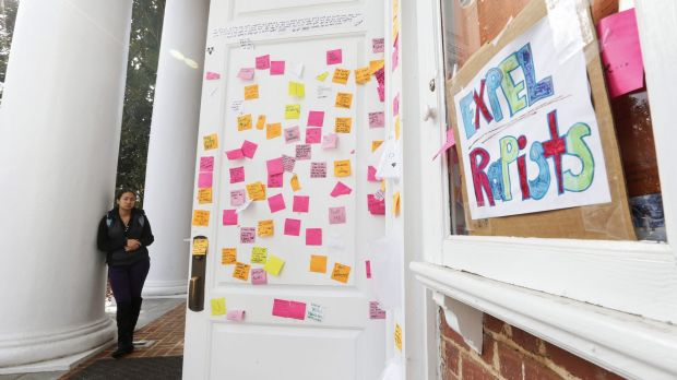 A University of Virginia student looks over postings on the door of Peabody Hall related to the Phi Kappa Psi gang rape ...