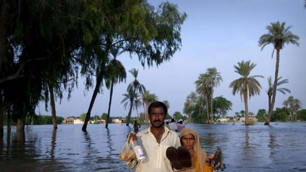 A couple wades through floodwaters in Punjab province. <i>Picture: Reuters</i>