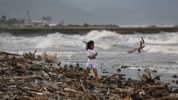 A girl walks along the shore as strong waves from Typhoon Hagupit hit Atimonan in the eastern Philippines.