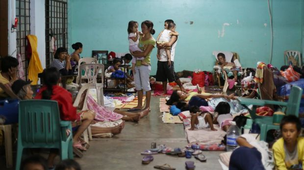 Filipino families seek refuge at a school used as an evacuation centre.