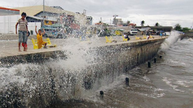 Wild weather: Waves brought by Typhoon Hagupit hit a concrete barrier along the Boulevard Seaport in Surigao City, ...