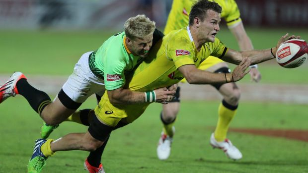 Under pressure: Con Foley of Australia gets a pass away in a tackle.