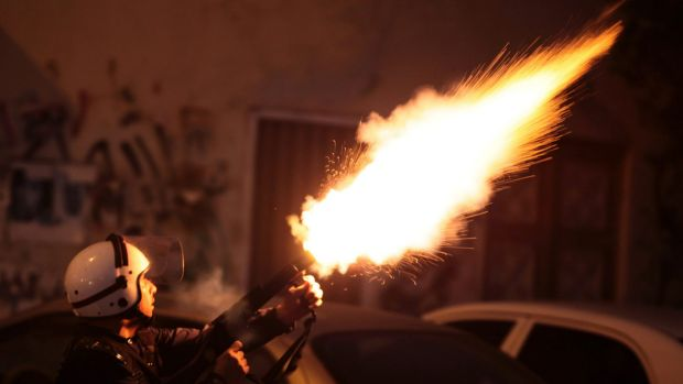 A riot policeman fires tear gas to disperse protesters in Bahrain in September 2013. Britain has announced closer ...