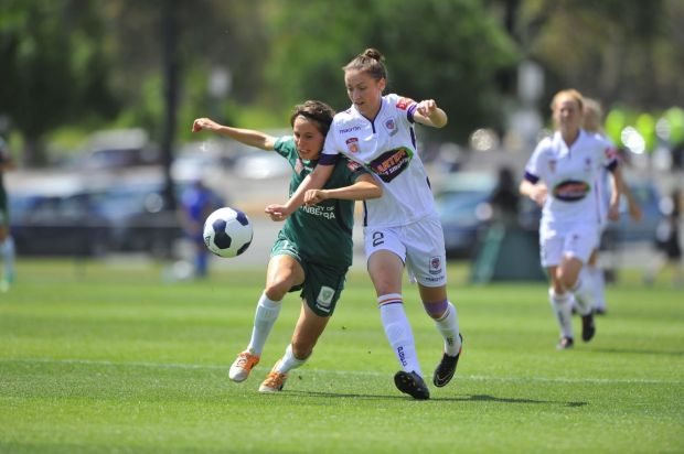 Canberra united player Ashleigh Sykes and Perth Glory player Sarah Carroll in action.