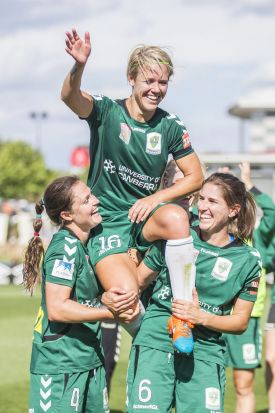 Canberra United player, Lori Lindsey is lifted on the shoulders of Kendall Fletcher and Caitlin Munoz after the game.