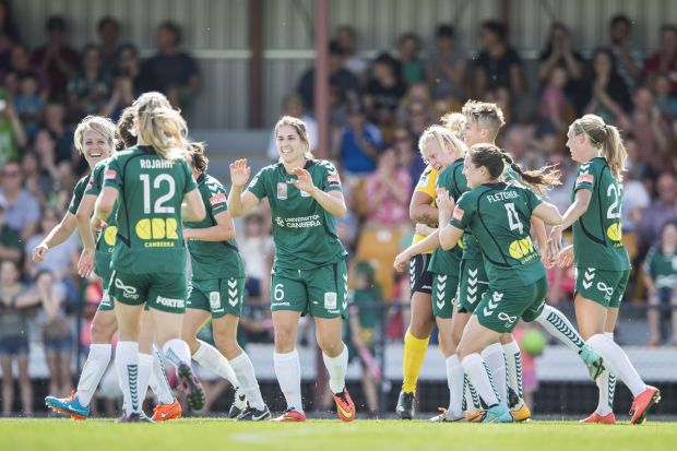 Canberra United players celebrate Ashleigh Skyes' winning goal late in the game.
