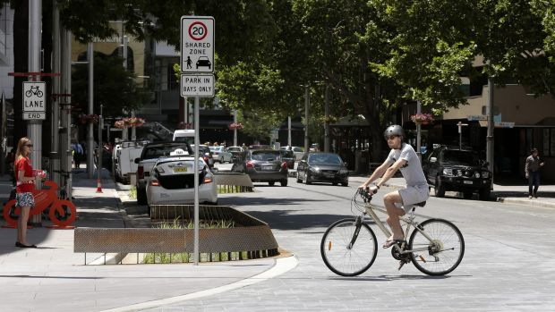 Student Clinton Madden rides his bike across one of the raised intersections on Bunda Street.