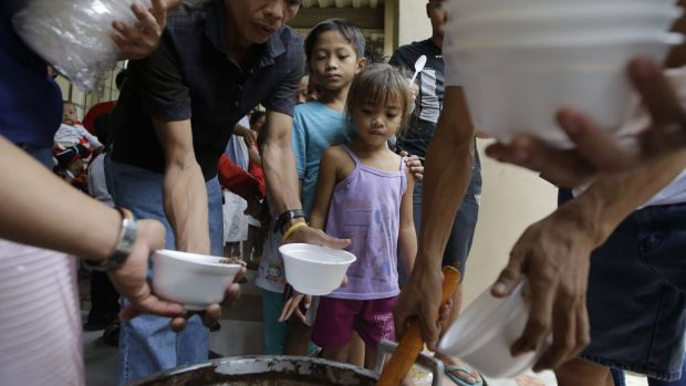 Evacuated children receive free chocolate rice porridge as they seek shelter at an evacuation centre.