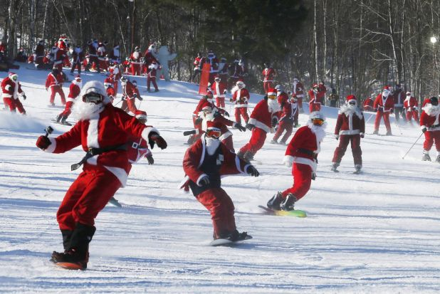 Skiers and snowboarders dressed as Santa participate in a charity run down a slope at Sunday River Ski Resort in Newry, ...