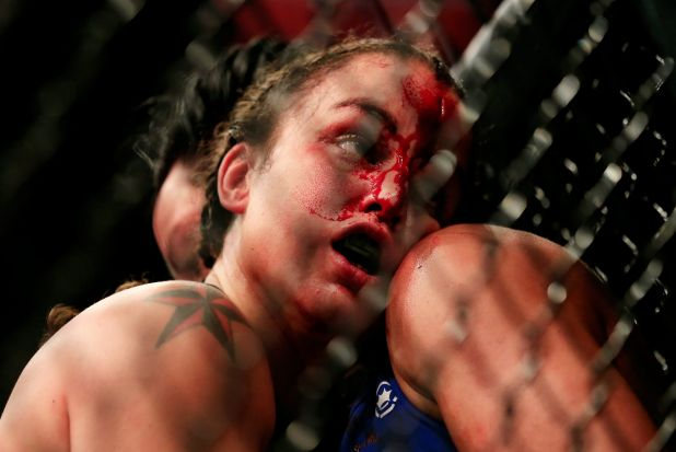 Raquel Pennington and Ashlee Evans-Smith grapple against the cage in their fight during the UFC 181 event at the ...