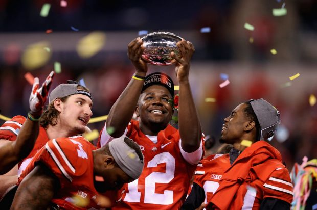 Quarterback Cardale Jones of the Ohio State Buckeyes lifts the Big Ten trophy after his team defeated the Wisconsin ...