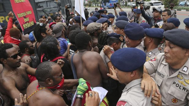 Activists scuffle with police during a rally marking the 53rd anniversary of the Free Papua Movement in Jakarta on ...