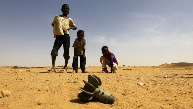 Children look at the fin of a mortar projectile that was found at the Al-Abassi camp for internally displaced persons, ...