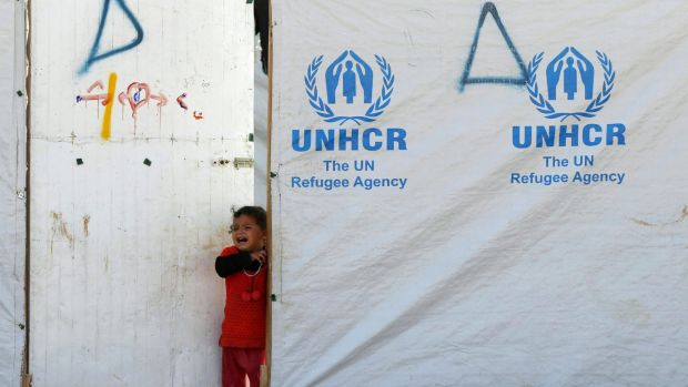 A Syrian refugee girl cries at a tent at the Al Zaatari refugee camp in the Jordanian city of Mafraq, near the border ...