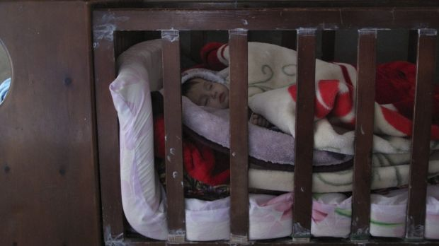 Make-do: Six-month-old Kareema sleeps in a borrowed cot, blankets piled high in an attempt to keep out the cold.