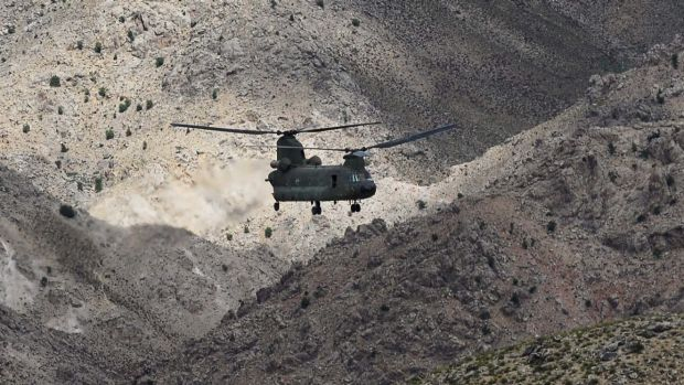 The mountainous terrain of Afghanistan dwarfs a CH-47D Chinook helicopter during a combat resupply mission in southern ...