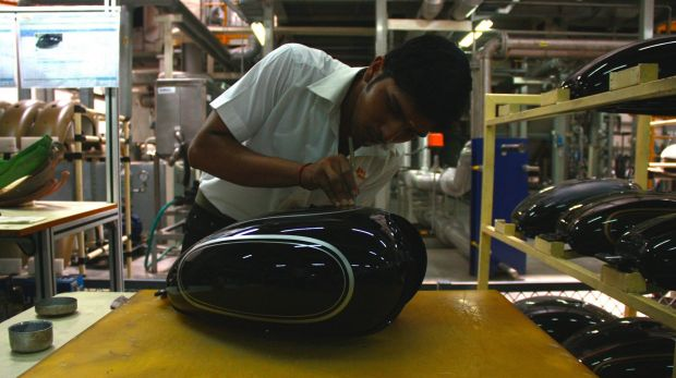 A worker paints a fuel tank.