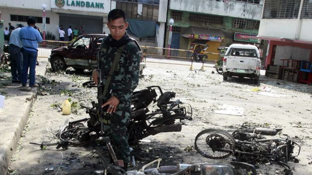 Ongoing terror campaign ... A Filipino soldier inspects the remains of motorcycles after bombings in Isabela, Basilan in ...