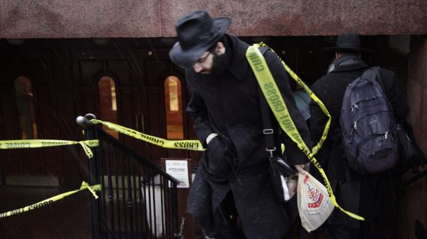 A member of the Chabad community walks through crime scene tape at the movement's headquarters in Crown Heights, Brooklyn.